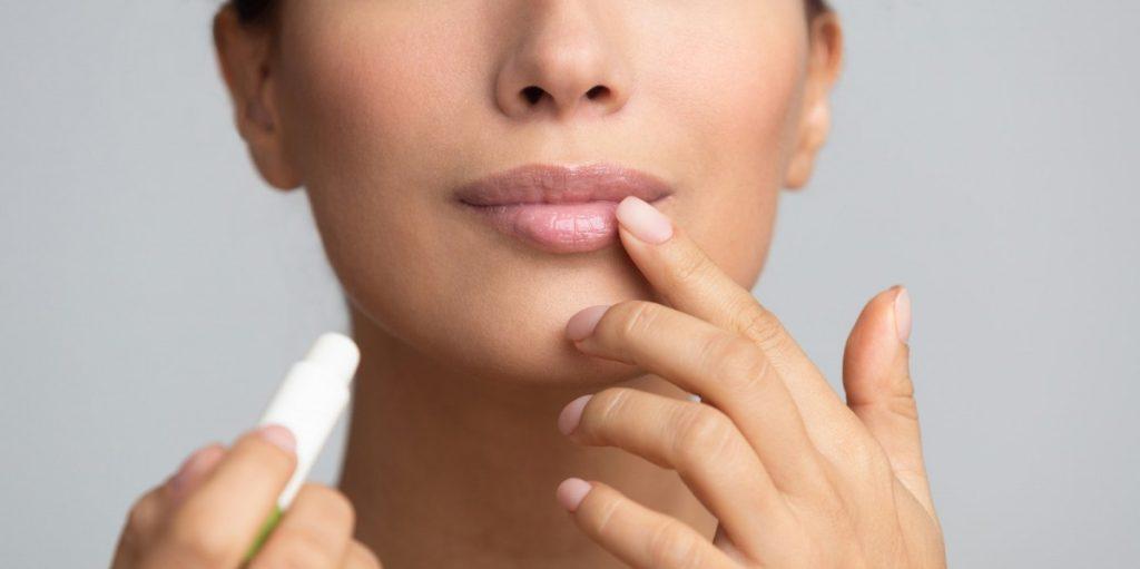 Lips skin care. Afro woman applying lip balm