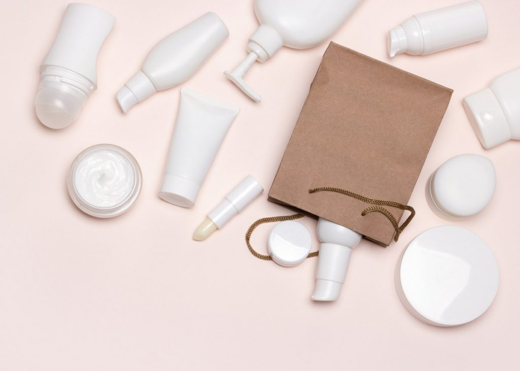 Various cosmetics and paper merchandise bag flatlay