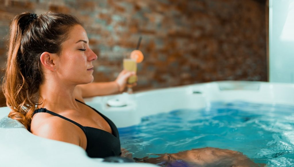 25 Incredible Benefits Of A Spa (Day, Treatments, Tub, Pool); Beautiful Woman Enjoying Jacuzzi in Spa Center.