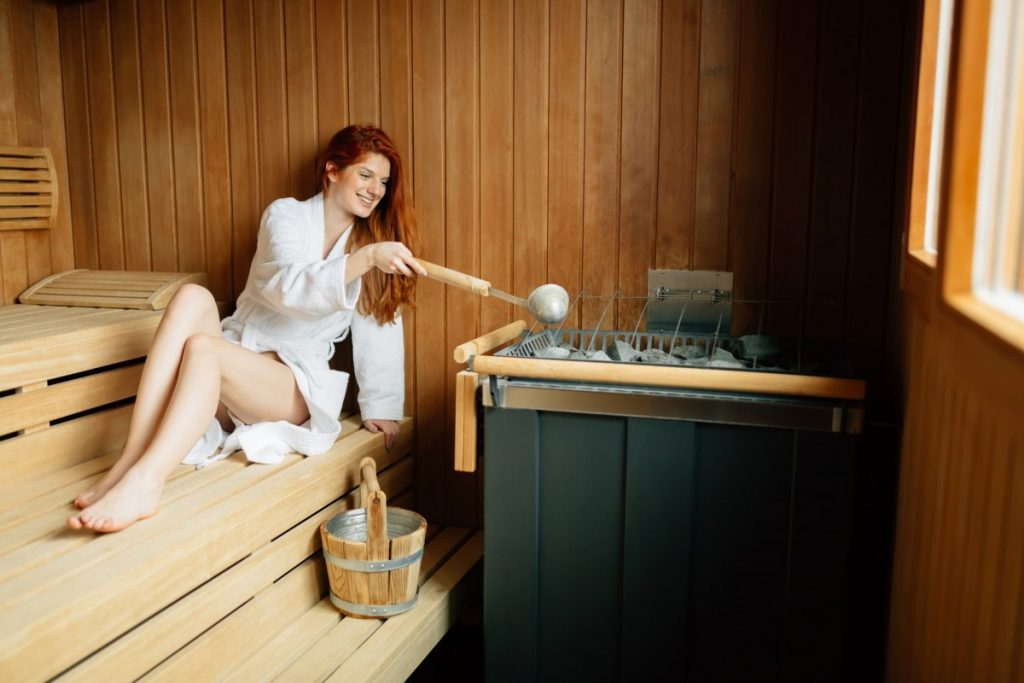 25 Incredible Benefits Of A Spa (Day, Treatments, Tub, Pool); Beautiful woman relaxing in finnish sauna