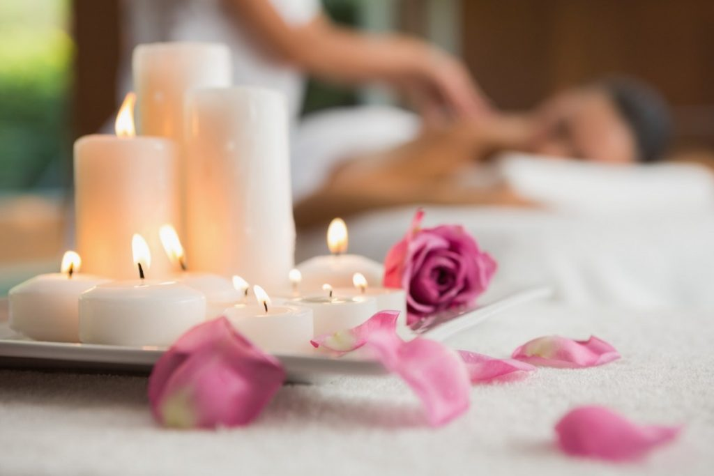 23 Ways To Make A Luxurious DIY Home Spa Bath On A Budget; Candles and rose petals on massage table at the health spa