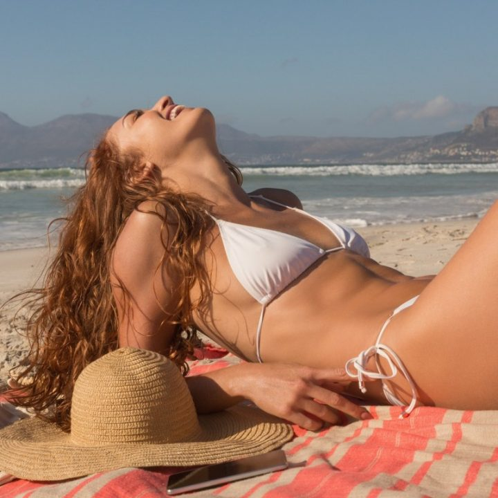 Gorgeous happy young Caucasian woman in bikini tanning lying on the beach.