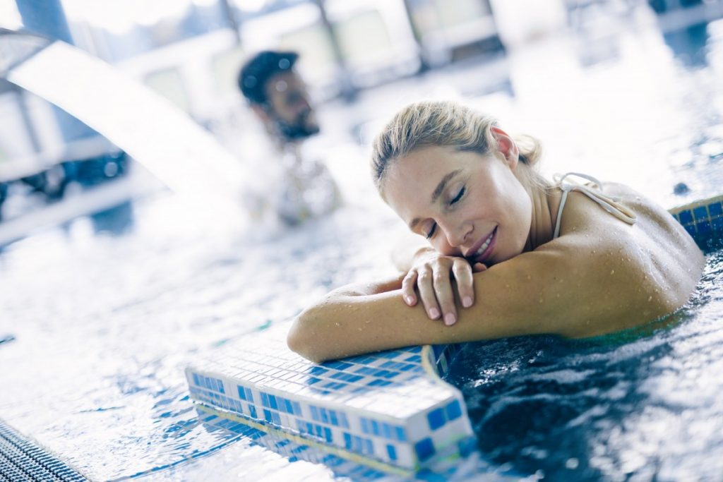 25 Incredible Benefits Of A Spa (Day, Treatments, Tub, Pool); Portrait of beautiful woman relaxing in swimming pool