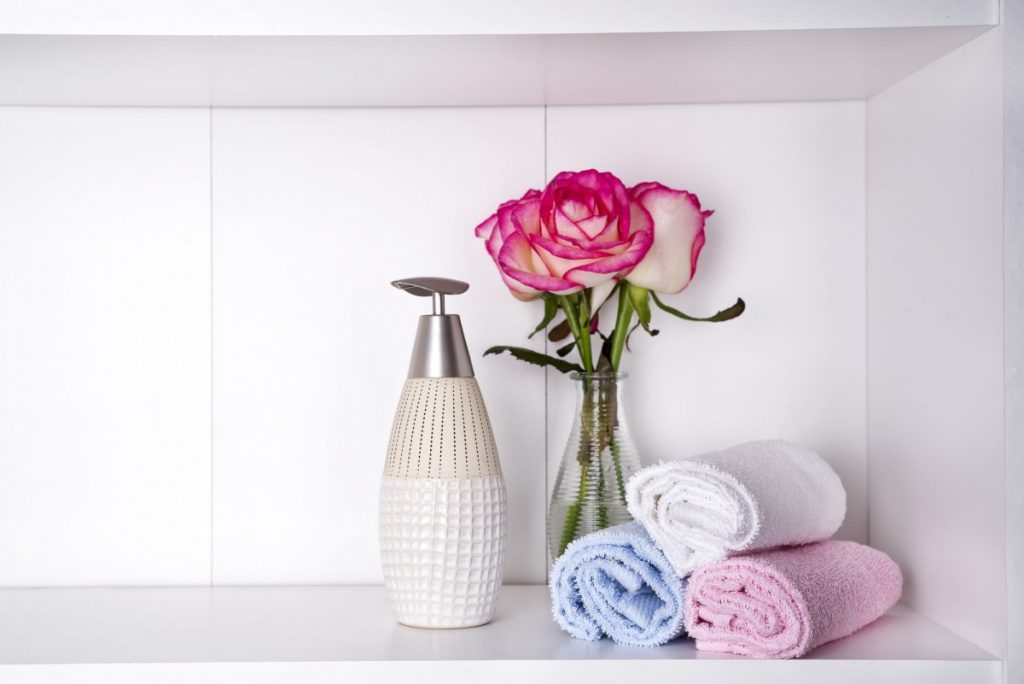 23 Ways To Make A Luxurious DIY Home Spa Bath On A Budget; Stack of towels with a soap dispenser and roses in vasein a bathroom closeup