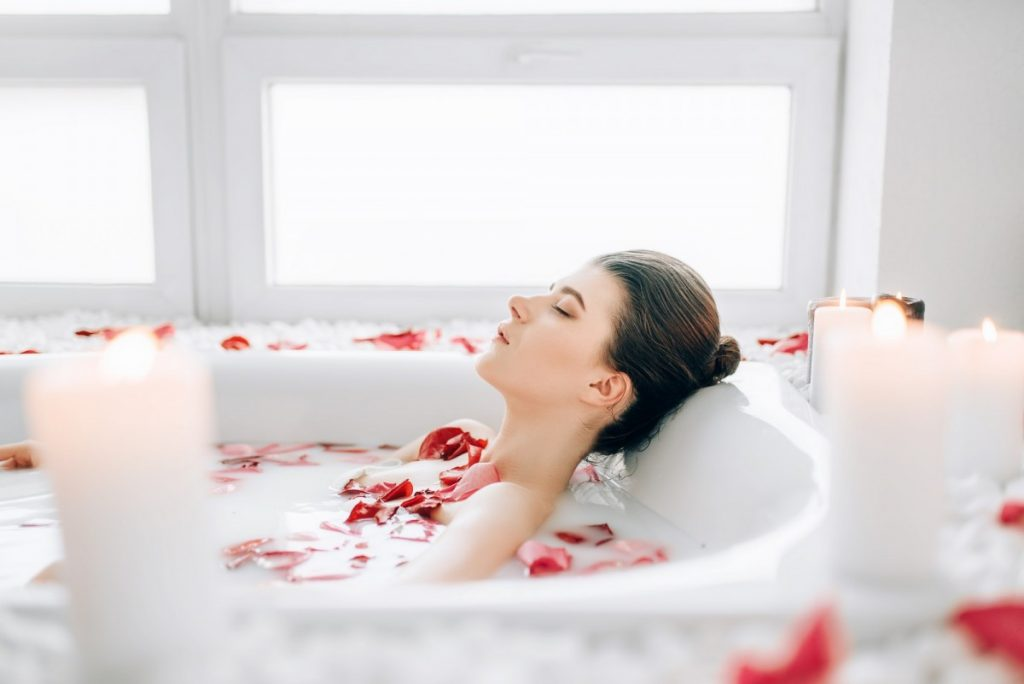 23 Ways To Make A Luxurious DIY Home Spa Bath On A Budget; Woman sleeps in the bath with foam, rose petals