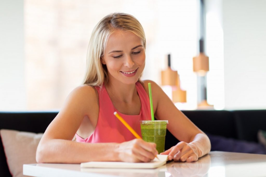 13 Ways To Look 10 Years Younger Naturally Without Costing The Earth; woman with drink writing to notebook at restaurant