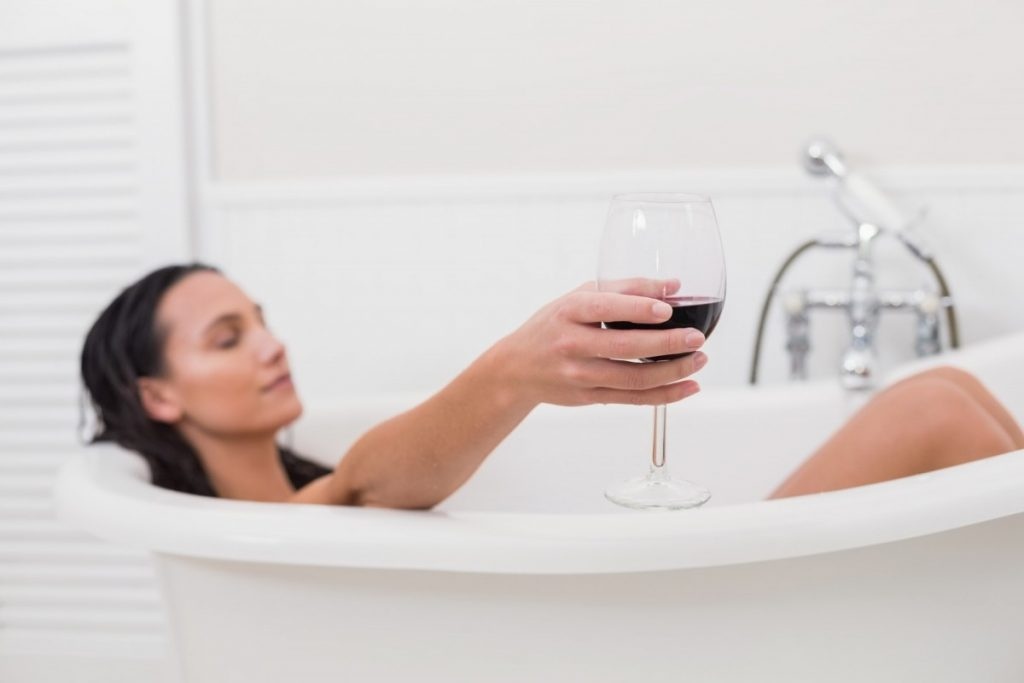 How To Have The Best At Home Spa Day: 25 Genius Ideas; Pretty brunette taking a bath with glass of wine in a bathroom