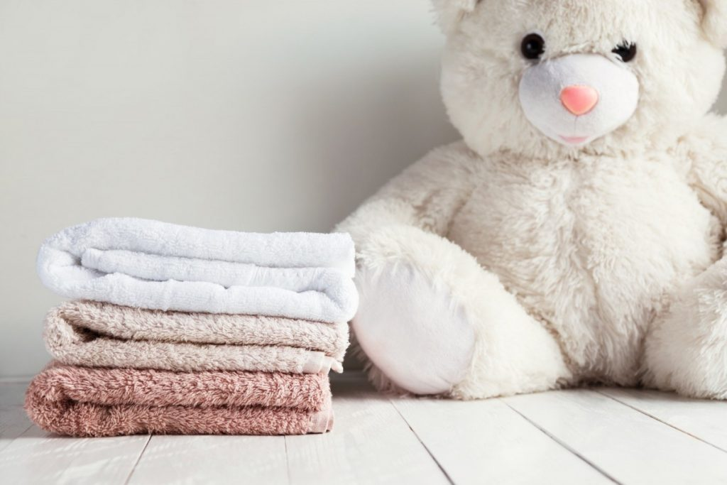 How To Have The Best At Home Spa Day: 25 Genius Ideas; Stack of spa towels on white wooden table with white soft toy bear on background