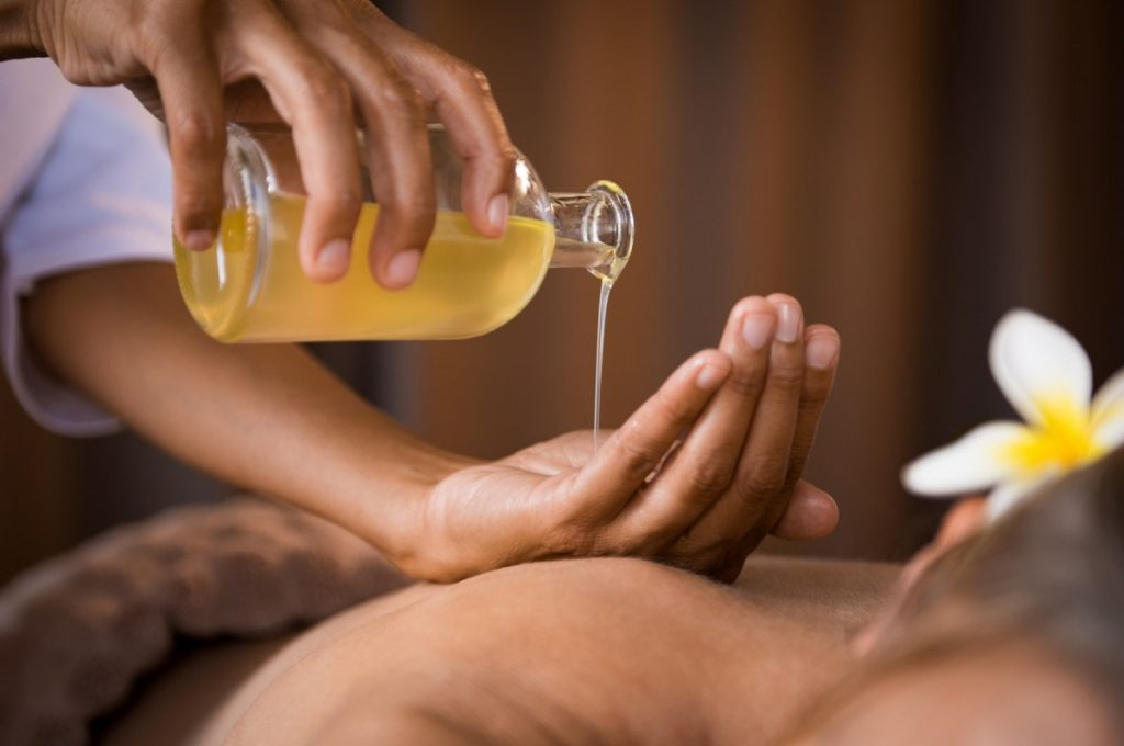 4 Best DIY Tanning Oil Recipes: Natural Protection With SPF; Therapist pouring massage oil at spa