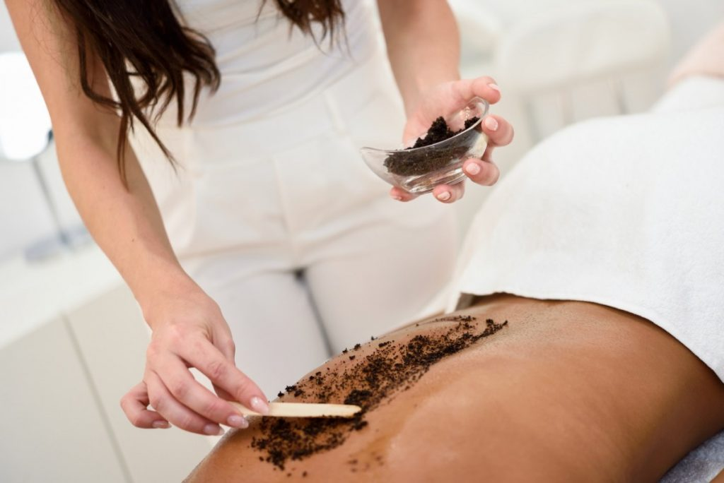 How To Have The Best At Home Spa Day: 25 Genius Ideas; Woman cleans skin of the body with coffee scrub in spa wellness