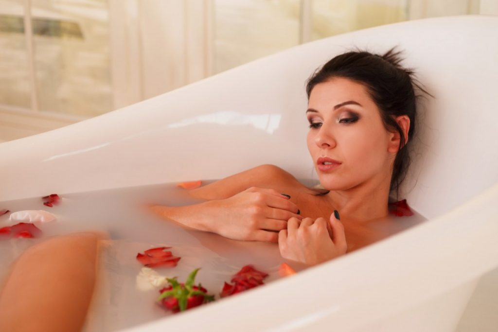 How To Have The Best At Home Spa Day: 25 Genius Ideas; Young attractive woman relaxing in bath with foam and petals.