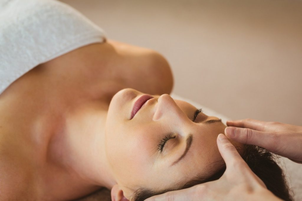 How To Have The Best At Home Spa Day: 25 Genius Ideas; Young woman having a reiki treatment in therapy room