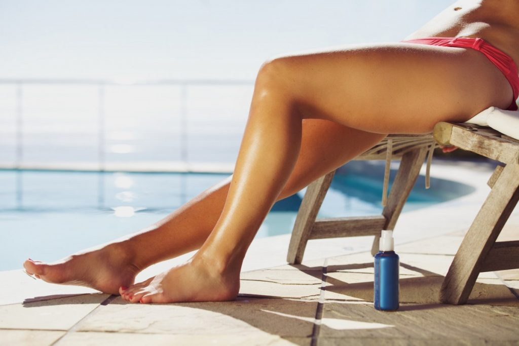 4 Best DIY Tanning Oil Recipes: Natural Protection With SPF; Young woman sunbathing by the poolside