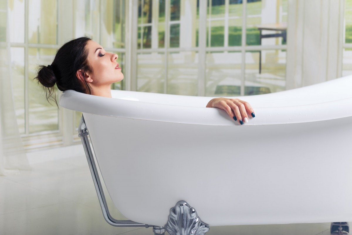 7 Best Bath Tea Bags That Heal All Skin Types; Bathing woman relaxing in bath smiling relaxing with eyes closed