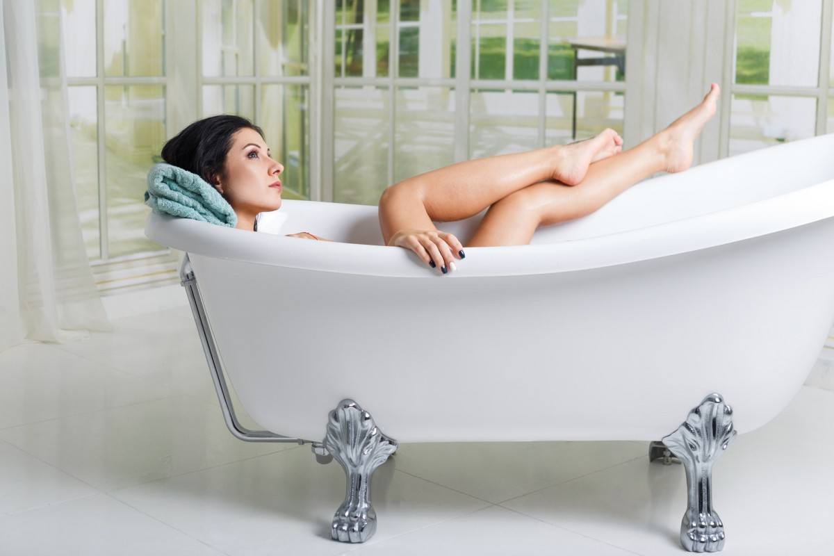 7 Best Bath Tea Bags That Heal All Skin Types; Beautiful young woman taking care about legs lying in the bathtube in the bathroom