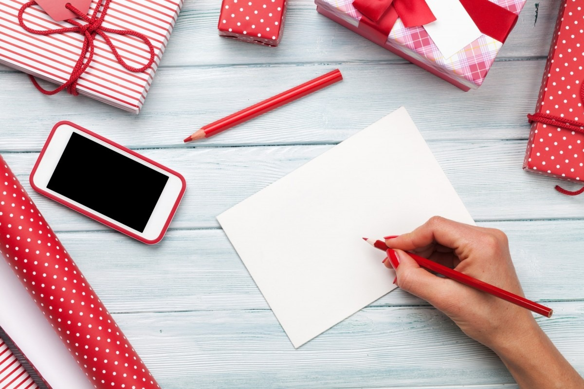 25 DIY Spa Gifts That Show How Much You Care; Female writing greeting card and wrapping christmas gifts