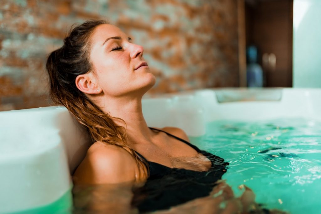 15 Mind Blowing Home Spa Ideas For Complete Pampering; Young Woman in Jacuzzi.