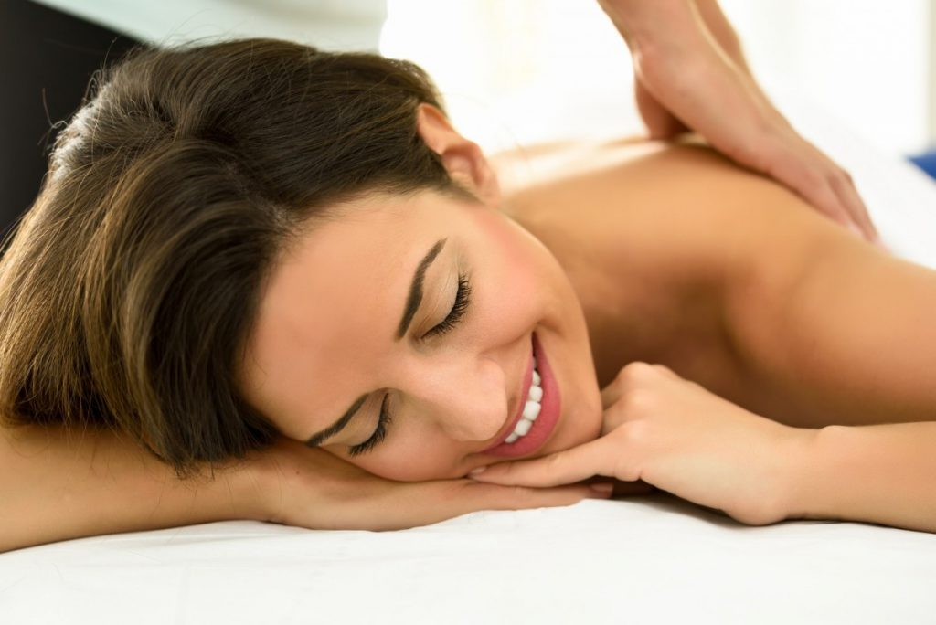 15 Mind Blowing Home Spa Ideas For Complete Pampering; Young woman receiving a back massage in a spa center.