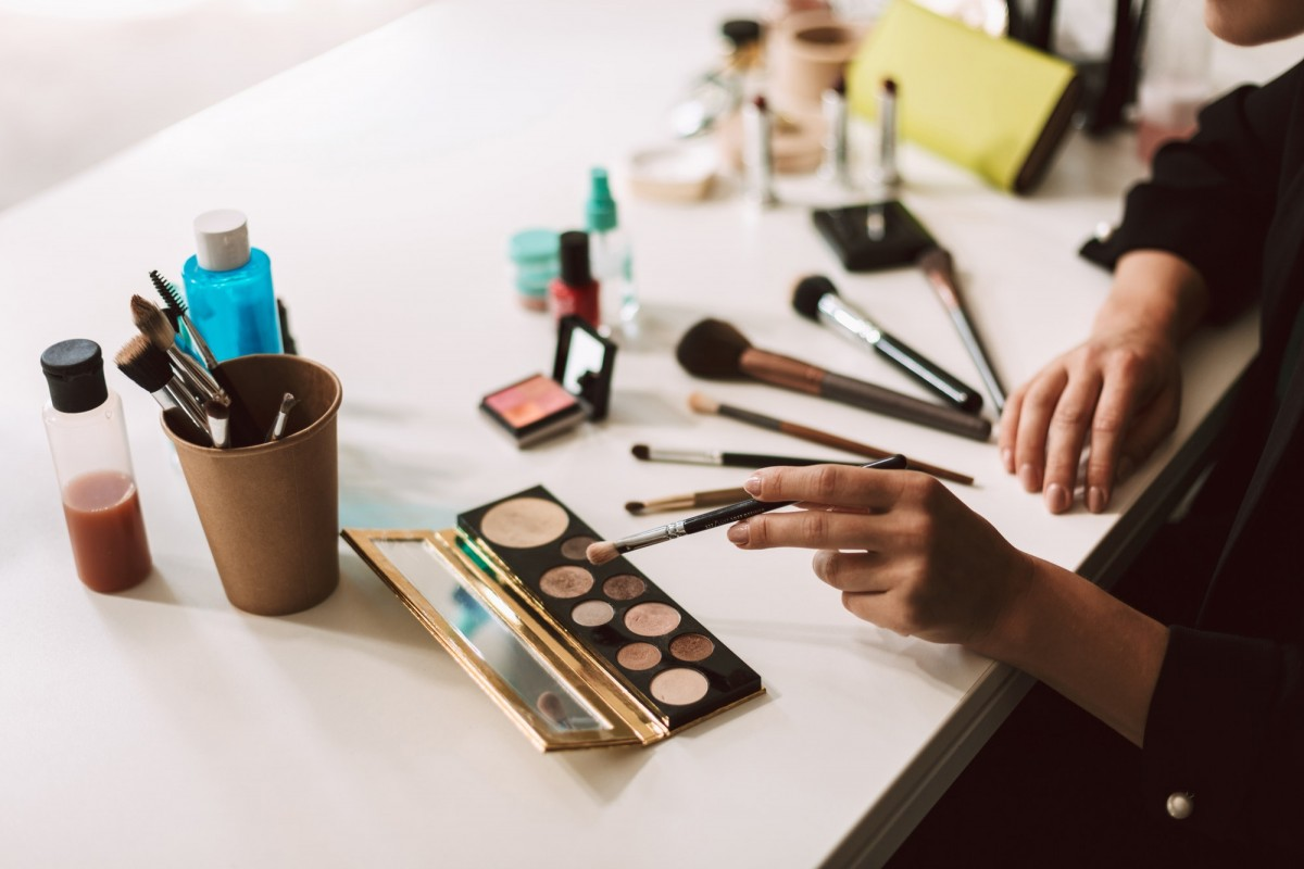 25 Toxic Skincare Ingredients To Avoid In Your Own Cosmetics; Close up make up artist sitting at the desk withbvariety of cosm