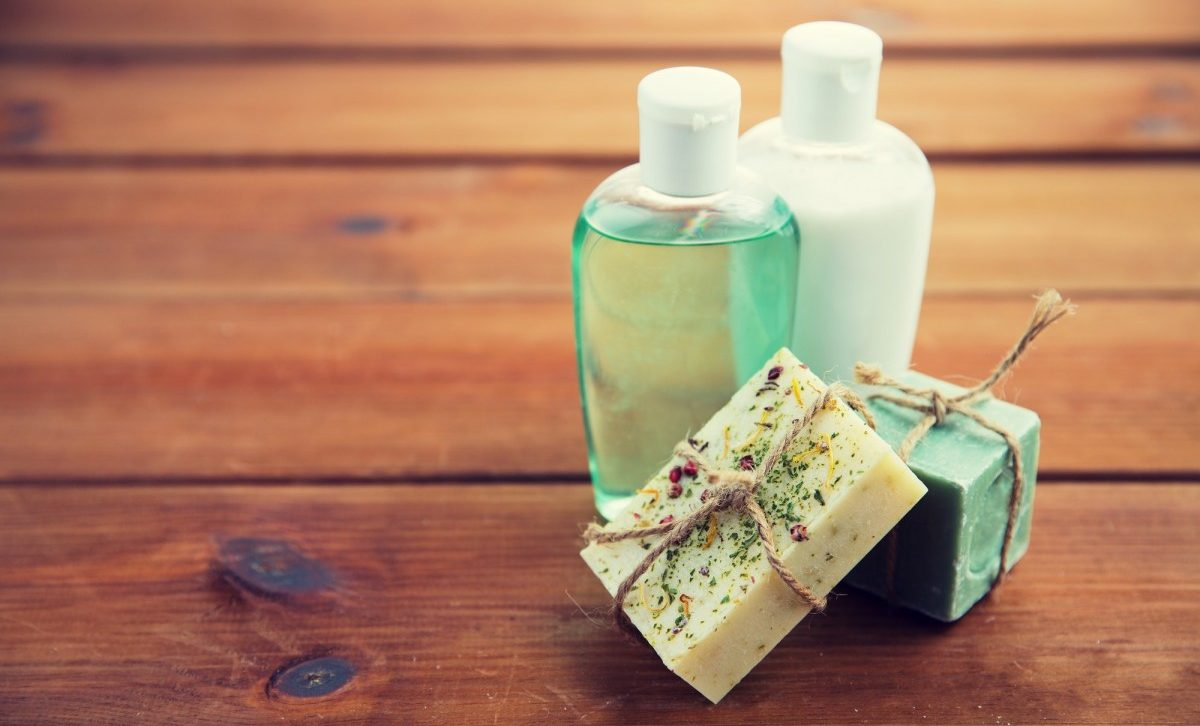 25 Easy DIY Spa Recipes That Will Make You Look 10 Years Younger; close up of handmade soap bars and lotions on wood