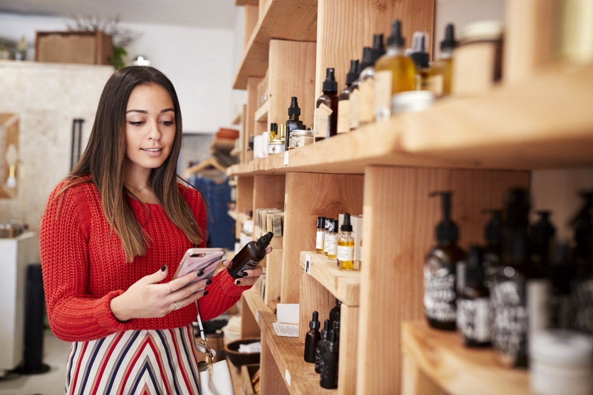25 Toxic Skincare Ingredients To Avoid In Your Own Cosmetics; Female Customer Shopping In Independent Cosmetics Store Comparing Prices Using Mobile Phone