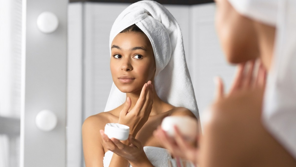 25 Toxic Skincare Ingredients To Avoid In Your Own Cosmetics; Girl Holding Face Cream Product Hydrating Skin In Bathroom