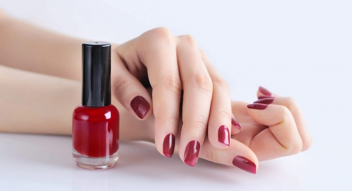 25 Toxic Skincare Ingredients To Avoid In Your Own Cosmetics; Hands of a woman with dark red manicure and nail polish bottle