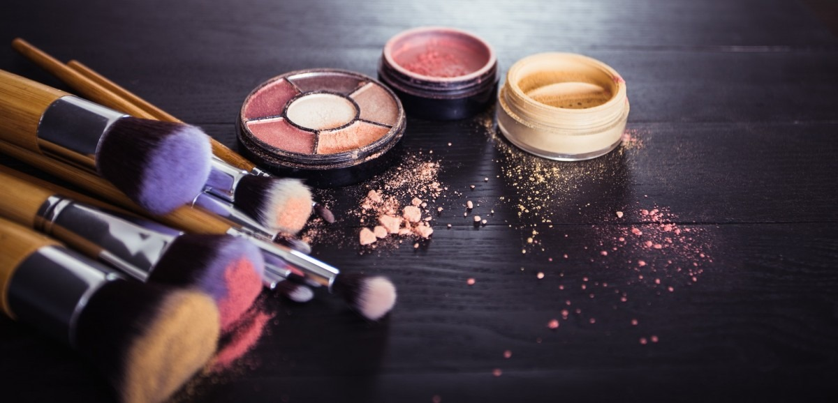 25 Toxic Skincare Ingredients To Avoid In Your Own Cosmetics; make up brushes with powder and rouge on a black wooden backgroud