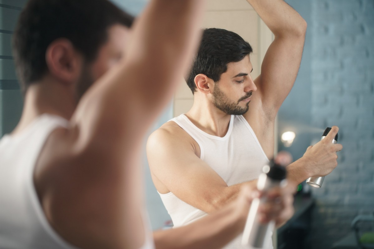 25 Toxic Skincare Ingredients To Avoid In Your Own Cosmetics; Man Using Spray Deodorant On Underarm For Bad Smell