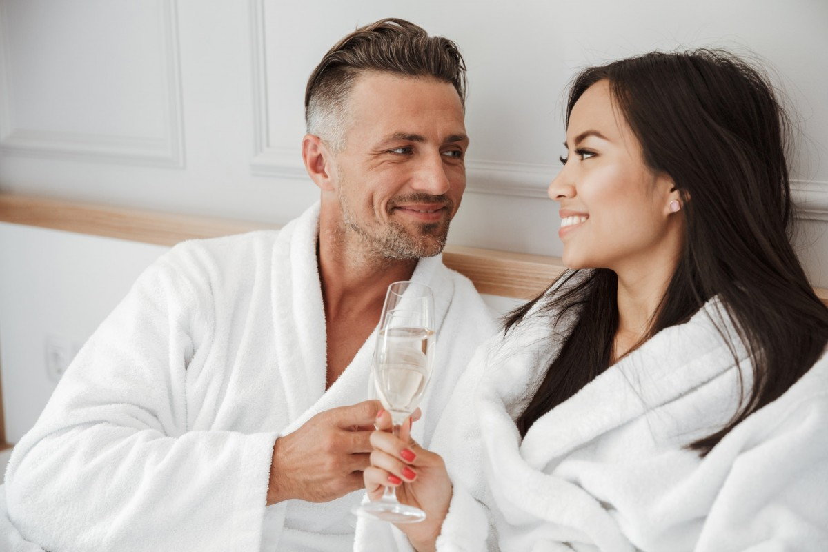 This DIY Spa Night Routine Will Give You A Youthful Glow; Romantic couple 30s caucasian man and asian woman wearing white