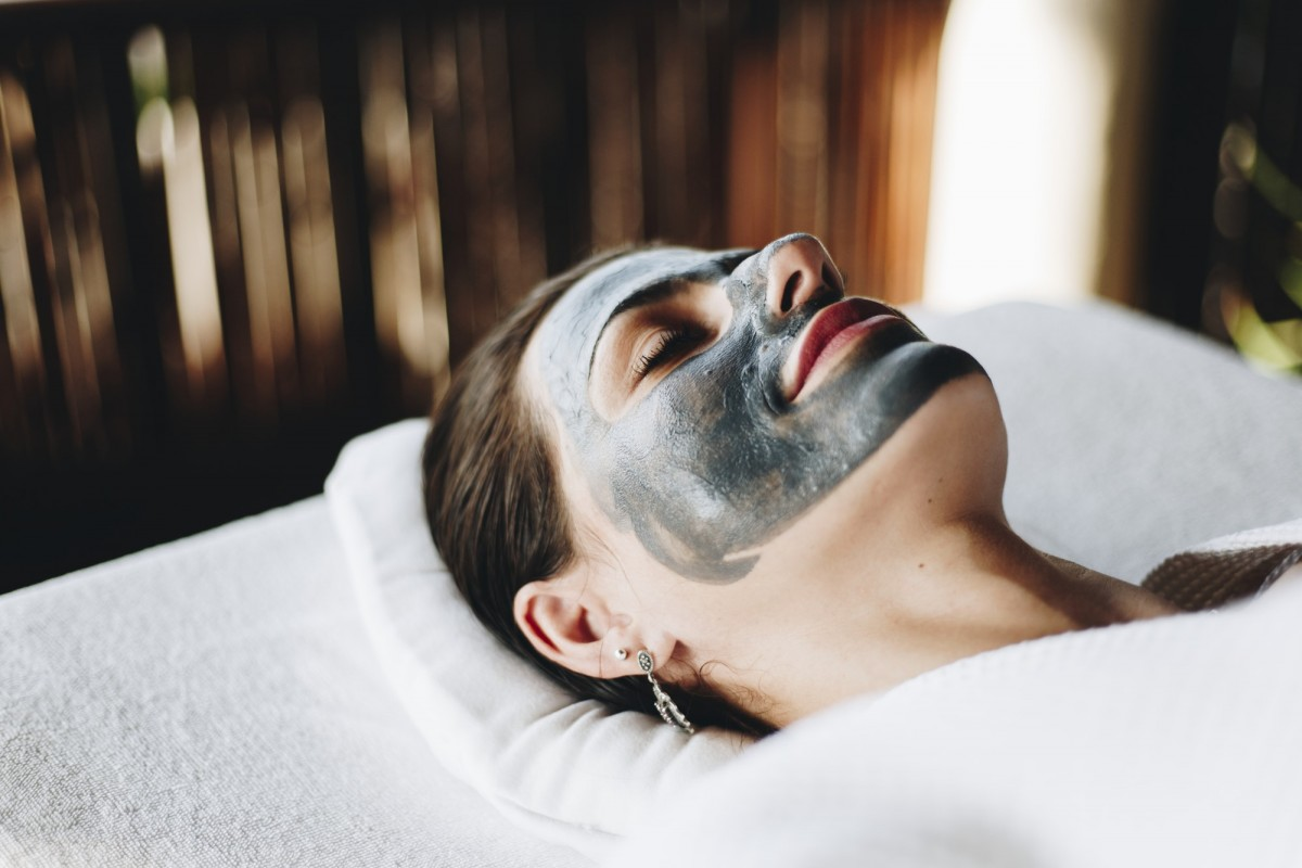 This DIY Spa Night Routine Will Give You A Youthful Glow; Woman relaxing with a facial mask at the spa