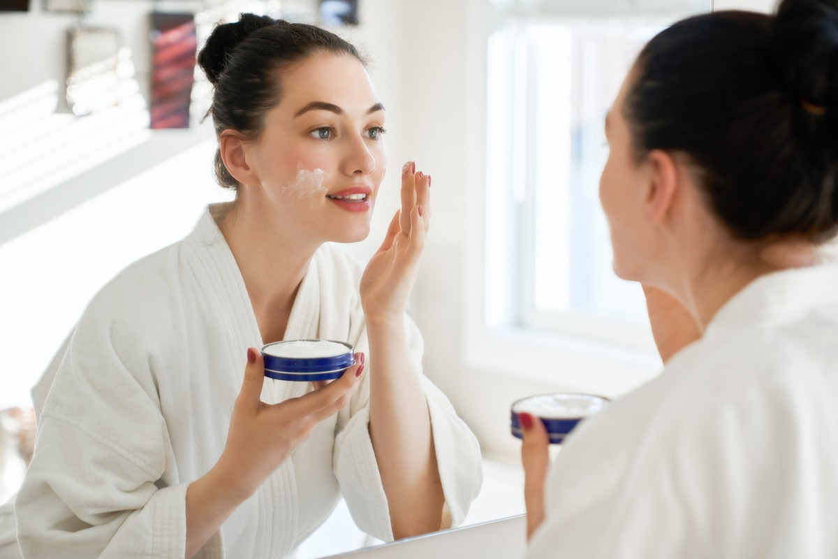 25 Easy DIY Spa Recipes That Will Make You Look 10 Years Younger; woman with cream for her face
