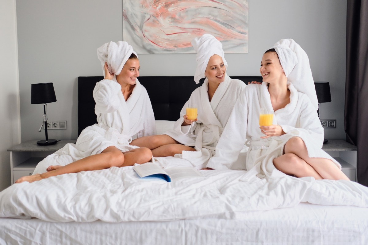 This DIY Spa Night Routine Will Give You A Youthful Glow; Young beautiful women in white bathrobes and towels on head happily talking together